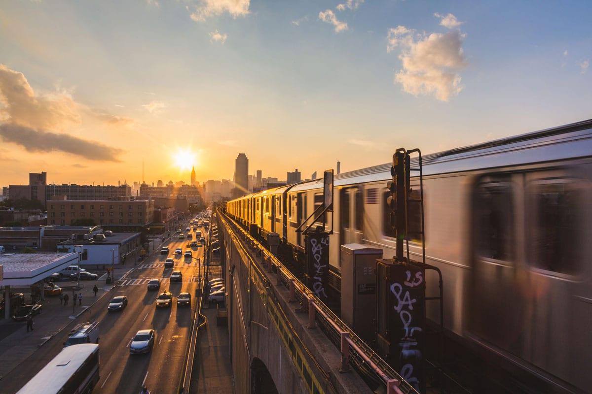 U-Bahn faehrt ueber Bruecke in New York bei Sonnenuntergang