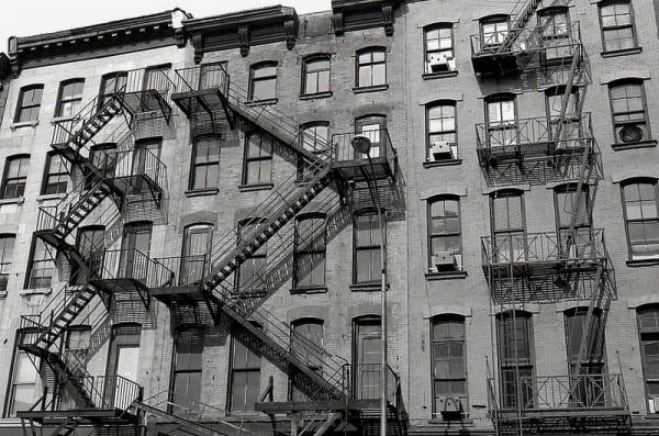 Schwarz-Weiß-Bild eines New Yorker-Wohnhauses mit den typischen Feuerleitern